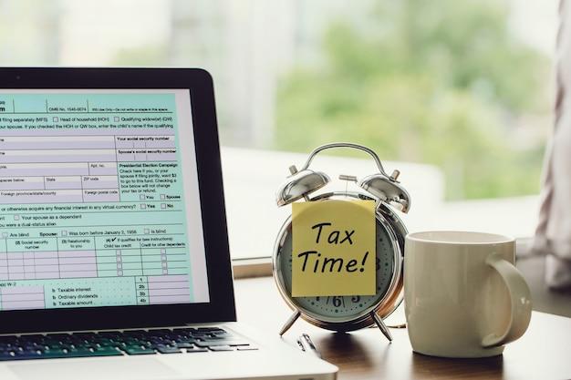 Concetto di tempo fiscale tempo fiscale su un postit sulla sveglia e modulo di dichiarazione dei redditi individuale online