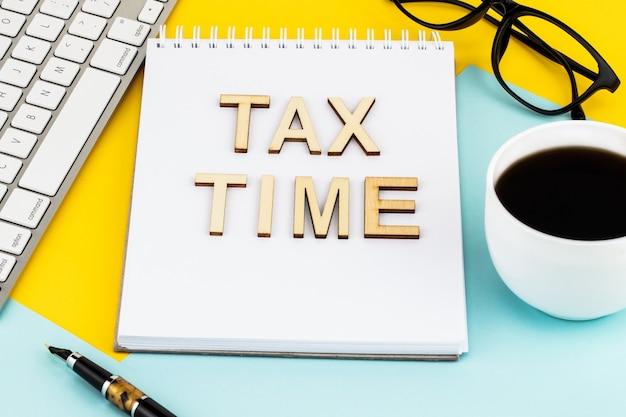 Tax time lettere in legno con modulo fiscale e tazza di caffè.
