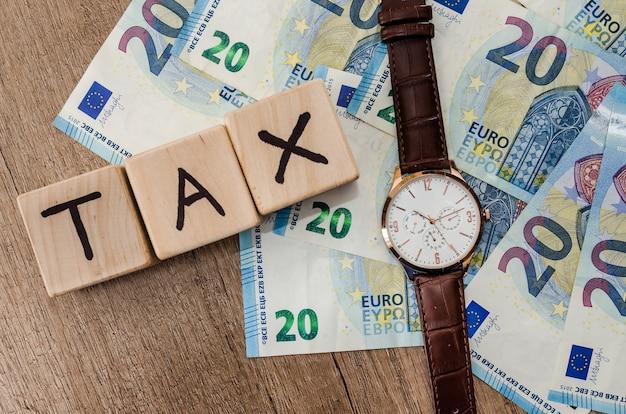 Cubi di legno fiscali con orologio su banconote in euro