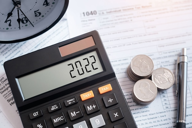 Parola fiscale e numero 2022 sulla calcolatrice. penna e moneta sul modulo fiscale 1040. tassa professionale. il concetto di imposta del nuovo anno 2022.