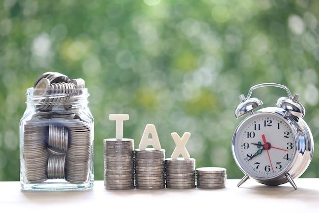 Parola fiscale sulla pila di monete denaro e bottiglia di vetro con sveglia su sfondo verde naturale, concetto di imposta sugli investimenti aziendali e sulla proprietà property