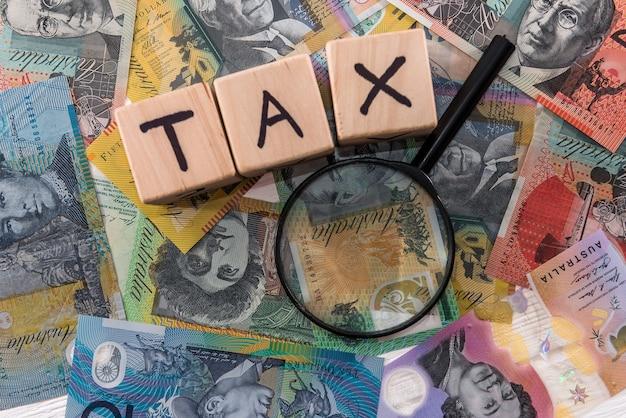 Concetto di tassazione, dollaro australiano con mattoni di legno