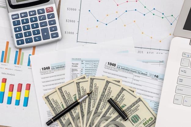 Concetto di tassazione, grafici commerciali con banconote in dollari e laptop