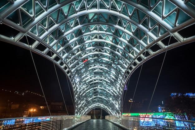 Tbilisi, georgia -: ponte pedonale della pace sul fiume mtkvari (kura) a tbilisi di notte. viaggio.