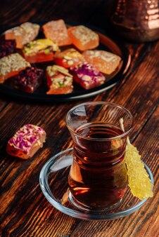 Tè in vetro armudu con delizie orientali rahat lokum su superficie in legno