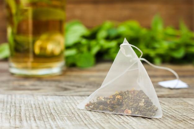 Bustina di tè su sfondo di menta e verde e tazza
