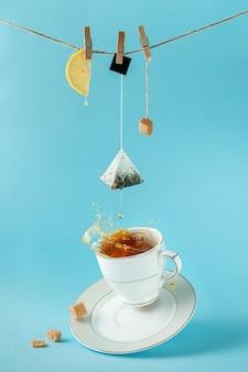 Bustina di tè, limone e zucchero appesi alla corda sopra schizzi di tè.