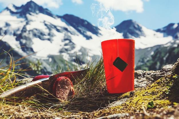 Bustina di tè in tazza di plastica arancione sullo sfondo del bellissimo paesaggio e dei laghi blu. romanticismo turistico escursionistico. colazione nella natura. coltello che taglia la salsiccia sull'erba