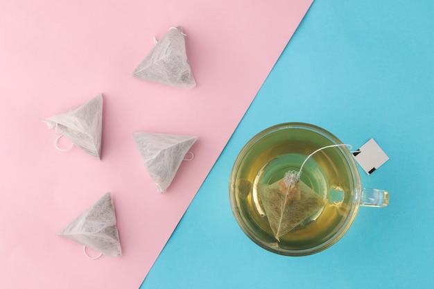 Piramide e tazza della bustina di tè con tè su un fondo blu e rosa delicato. per fare il tè. vista dall'alto