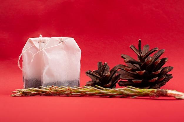 Primo piano delle bustine di tè con le pigne e un ramoscello dell'abete rosso su un fondo rosso. tè al gusto di bosco.