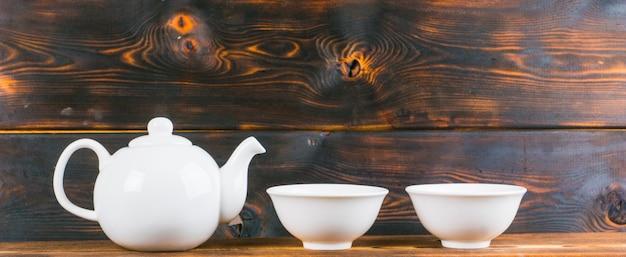 Ciotole e ciotola di tè sulla tavola di legno rustica