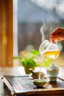 Processo di preparazione del tè, cerimonia del tè, una tazza di tè verde oolong appena preparato, calda luce soffusa.