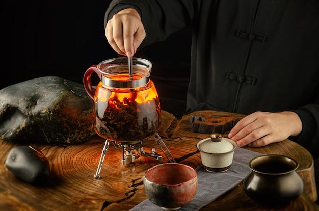 La cerimonia del tè, la preparazione del tè in fiamme in una teiera di vetro