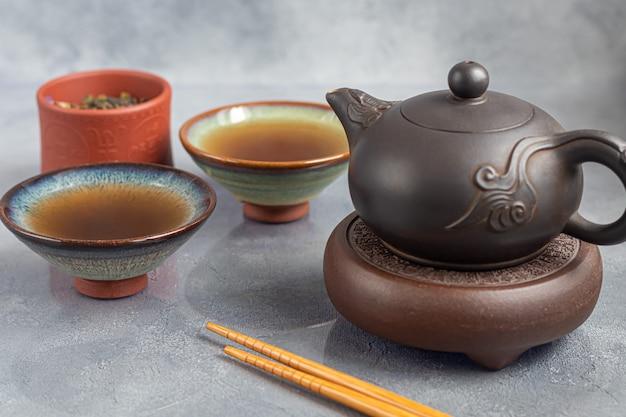 Cerimonia del tè. pu-erh cinese in una ciotola. in fondo è una teiera marrone e foglie di tè. copia spazio.