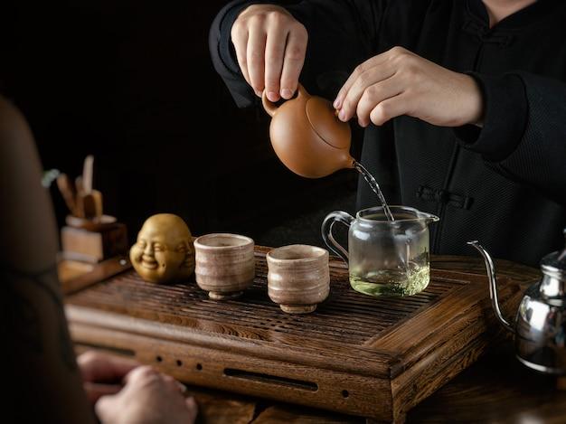 La cerimonia del tè aiuta uomini e donne a versare il tè Foto Premium