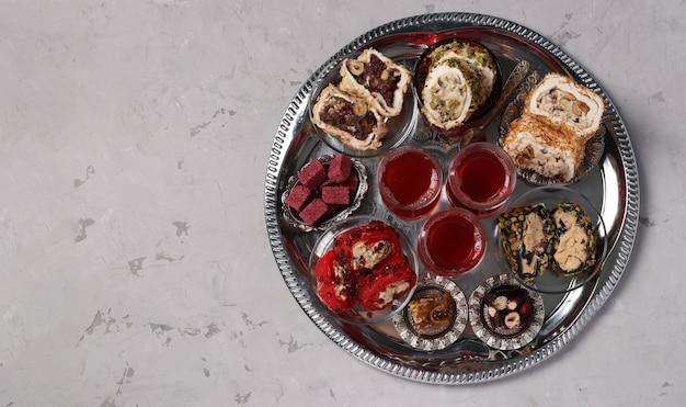Cerimonia del tè con un assortimento di dolci turchi su un vassoio rotondo di metallo su sfondo grigio