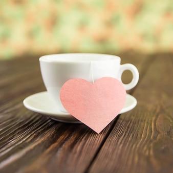 Cerimonia del tè con cuore sulla tavola di legno