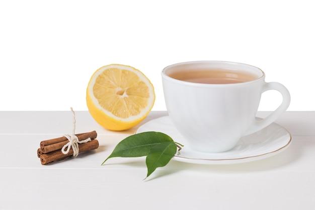 Tè, cannella e limone su un tavolo di legno bianco isolato su sfondo bianco. una bevanda tonificante utile per la salute.
