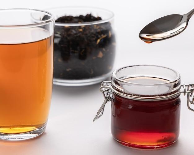 Concetto di tè, foglie di tè nero, bevanda del tè in tazza di vetro e miele in vaso sul tavolo, miele dorato in cucchiaio