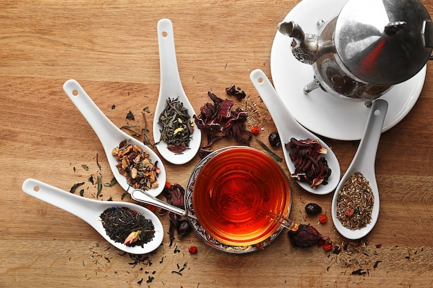 Il concetto di tè. diversi tipi di tè secco in cucchiai. tazza di vetro di tè su fondo in legno