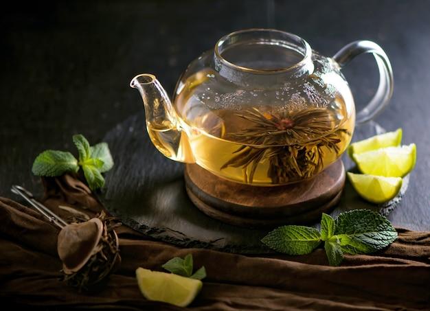 Concetto di tè, teiera con tè circondato su uno sfondo di legno, cerimonia del tè, tè verde in una tazza trasparente