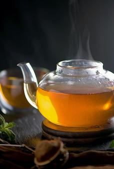 Concetto di tè, teiera con tè circondato su una superficie di legno, cerimonia del tè, tè verde in una tazza trasparente