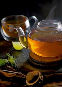 Concetto di tè, teiera con tè circondato sulla cerimonia del tè tavolo in legno, tè verde in una tazza trasparente