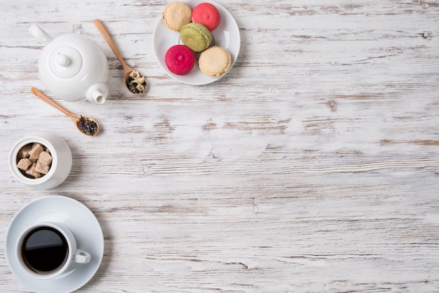 Tè, biscotti e zucchero su un tavolo bianco.