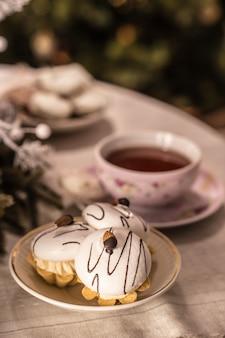 Tazza di tè e dolci sul tavolo davanti all'albero di natale