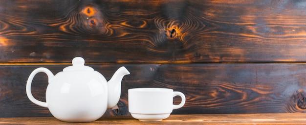 Tazza e pentola di tè sulla tavola di legno rustica