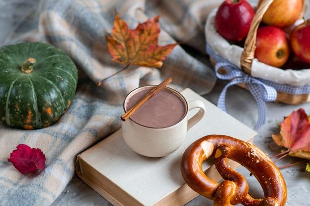 Tazza da tè con cioccolata calda autumn time bakery ciambellina salata sciarpa lavorata a maglia tonica coperta foglie gialle grigie