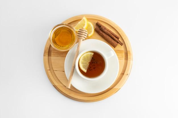 Tazza di tè con limone e miele su un bianco. tazza di tè calda isolata, disposizione piana di vista superiore. disteso. bevanda autunnale, autunnale o invernale. copyspace.