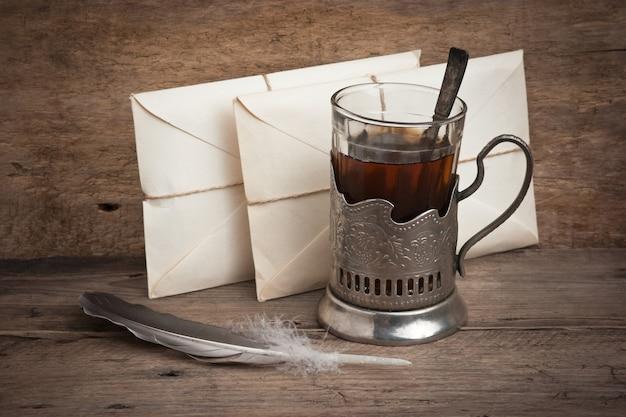 Tazza di tè con lettere su un tavolo di legno