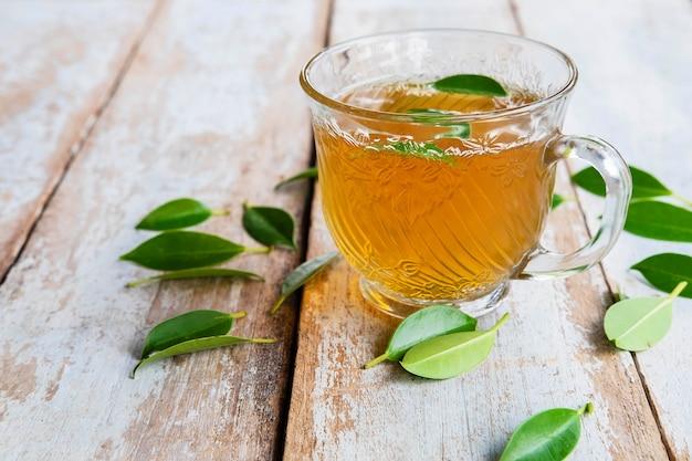 Tazze da tè e foglie di tè fresche su un tavolo di legno