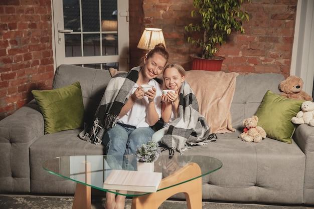 Bere il tè, parlare. madre e figlia durante l'autoisolamento a casa durante la quarantena.