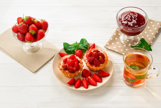Bere il tè con tortine e dolci alle fragole