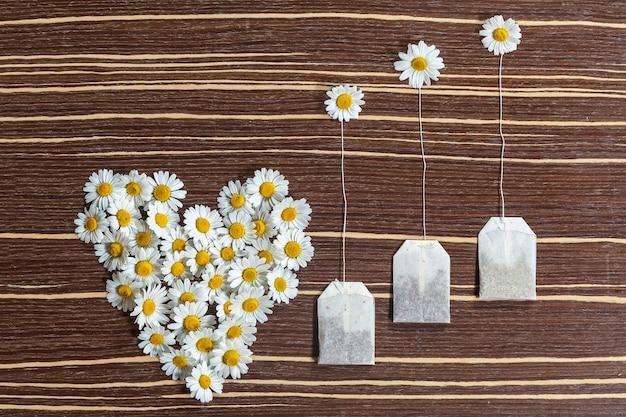 Composizione di tè e fiori l'originale composizione di tè e fiori su un tavolo in legno t