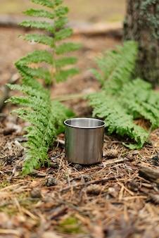 Tè del thermos nel bosco. tazza di tè in metallo. l'atmosfera della foresta.