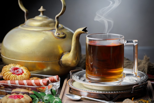 Bevanda calda del tè su vecchio fondo in composizione sulla tavola
