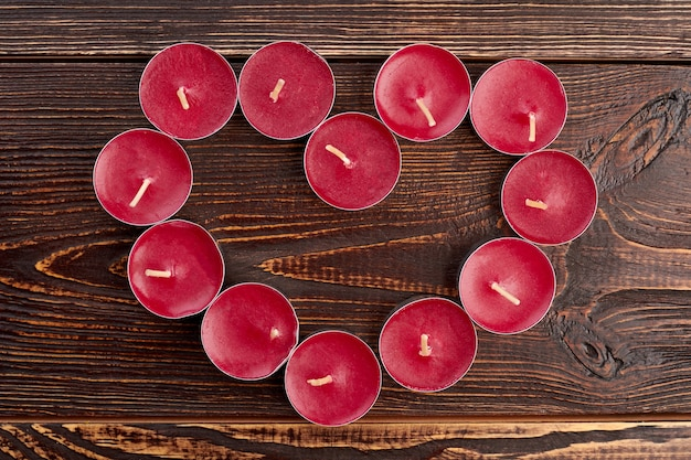 Candele di luce del tè che formano forma di cuore. vacanze di san valentino. concetto di tema di amore.