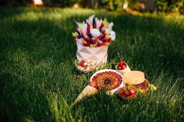 Tea party, dolci, bacche fresche e fiori sull'erba, nessuno. banchetto romantico all'aperto.