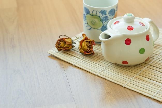 Teiera e tazza sul tavolo di legno.
