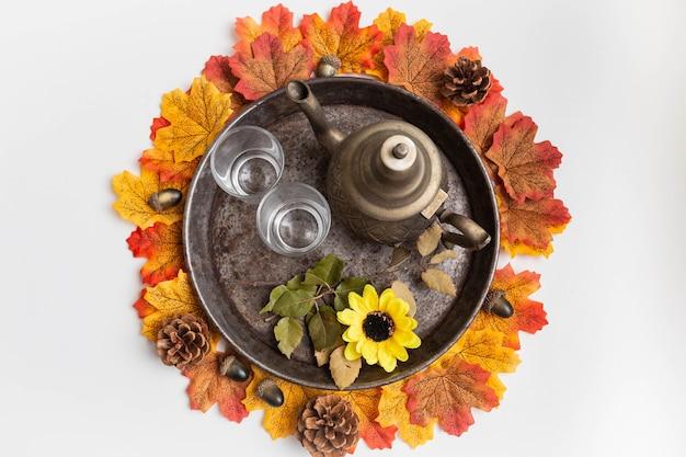 Servizio da tè su vassoio rustico circondato da foglie di acero ed elementi autunnali
