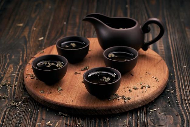 Servizio da tè e foglie di tè su tavola da cucina in legno