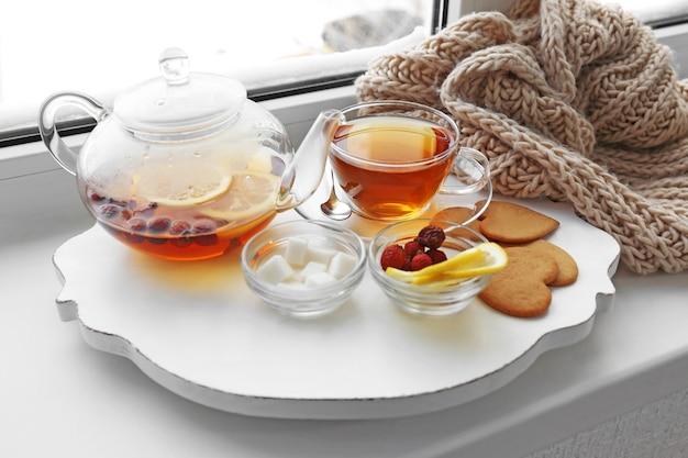 Servizio da tè su una stuoia di legno bianca sul davanzale della finestra