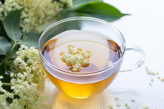 Tè e sciroppo di fiori di sambuco sambucus su uno sfondo bianco