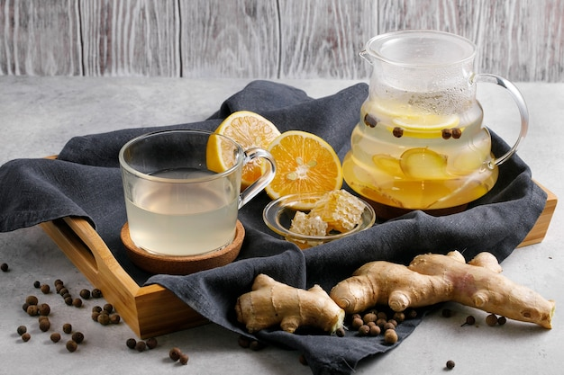Tè in teiera con radici di zenzero e fette di limone su grigio