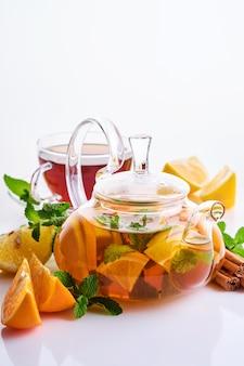 Tè in una teiera con fette di limone, arancia, menta e bastoncini di cannella isolati su un tavolo bianco.