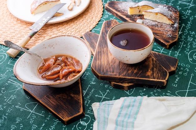 L'ora del tè, marmellata di albicocche, torta di ricotta e tazza di tè su assi di legno, formule matematiche su sfondo tovaglia.