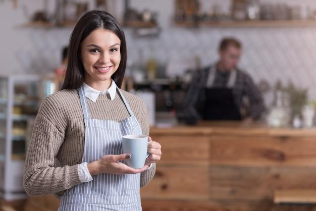 L'ora del tè. donna graziosa felice che sorride e che tiene tazza di tè mentre levandosi in piedi in un caffè.